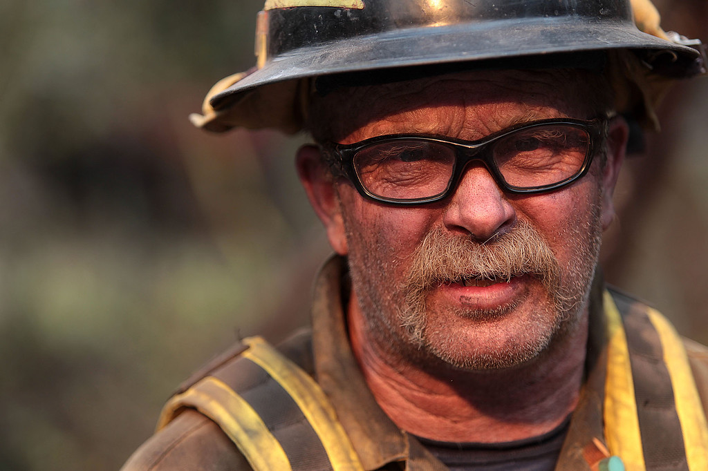 . David Hartman, with the Pagosa Fire Protection District in Colo., pauses while mopping up part of the 111,000 acre Elk Fire Complex near Pine, Idaho on Wednesday, Aug. 14, 2013. (AP Photo/Times-News, Ashley Smith)