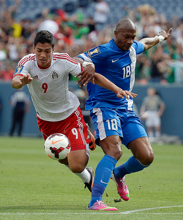. Gregory Arnolin #18 of Martinique pushes Luis Jimenez #9 of Mexico off the ball during the first half of the CONCACAF Gold Cup soccer game July 14, 2013 at Sports Authority Field at Mile High. (Photo By John Leyba/The Denver Post)