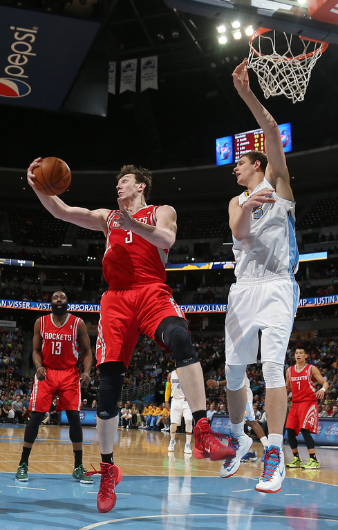 . Houston Rockets center Omer Asik, left, ot Turkey, pulls in rebound as Denver Nuggets center Timofey Mozgov, of Russia, covers in the third quarter of the Nuggets\' 123-116 victory in an NBA basketball game in Denver on Wednesday, April 9, 2014. (AP Photo/David Zalubowski)