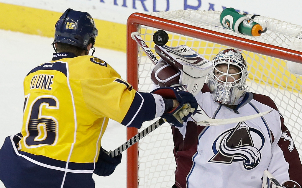 . Colorado Avalanche goalie Jean-Sebastien Giguere (35) blocks a shot as Nashville Predators left wing Rich Clune (16) closes in during the third period of an NHL hockey game Tuesday, April 2, 2013, in Nashville, Tenn. The Predators won 3-1. (AP Photo/Mark Humphrey)