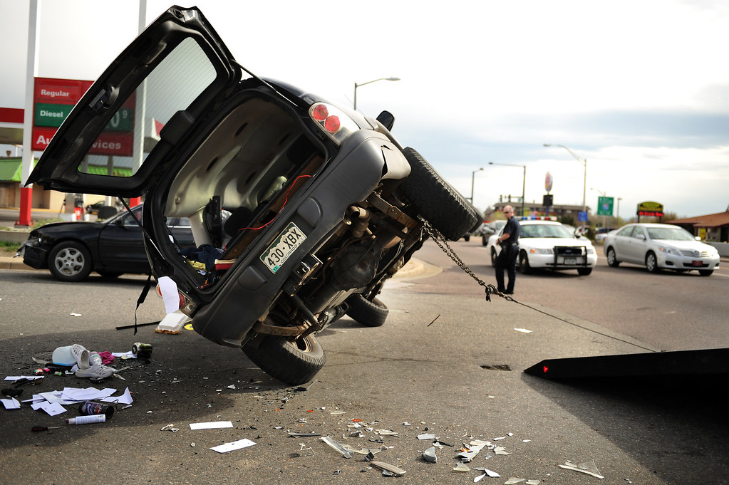 . Wreckers pull an SUV upright after a 3-car collision left one vehicle on its side at the corner of Federal Blvd & 49th Ave, in Denver, Colorado, Wednesday on April 18, 2012. At least one person was transported by ambulance from the accident. Joe Amon, The Denver Post