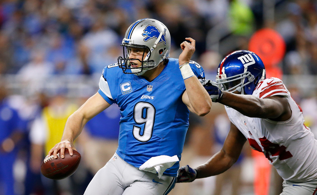 . Detroit Lions quarterback Matthew Stafford (9) is chased by New York Giants defensive end Mathias Kiwanuka (94) during the second quarter of an NFL football game, Sunday, Dec. 22, 2013, in Detroit. (AP Photo/Rick Osentoski)