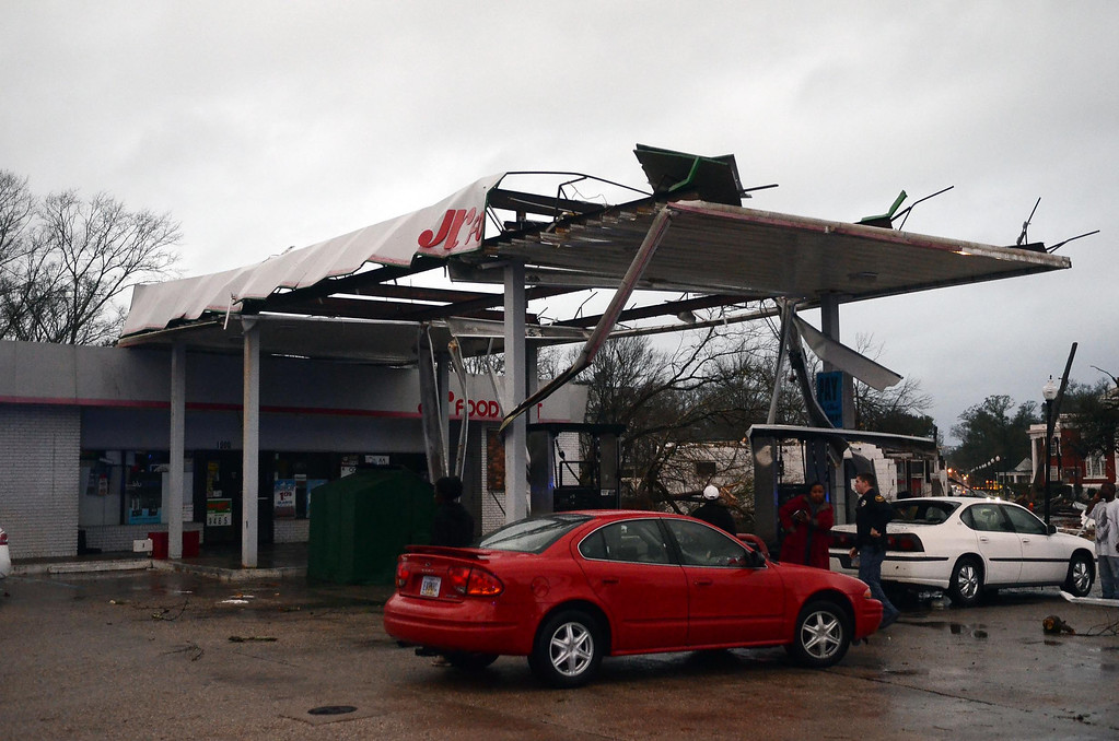 . Hattiesburg Police officers talk to onlookers at a damaged gas station in Hattiesburg, Miss. after an apparent tornado that moved through area on Sunday, Feb. 10, 2013. (AP Photo/The Hattiesburg American, Bryant Hawkins)