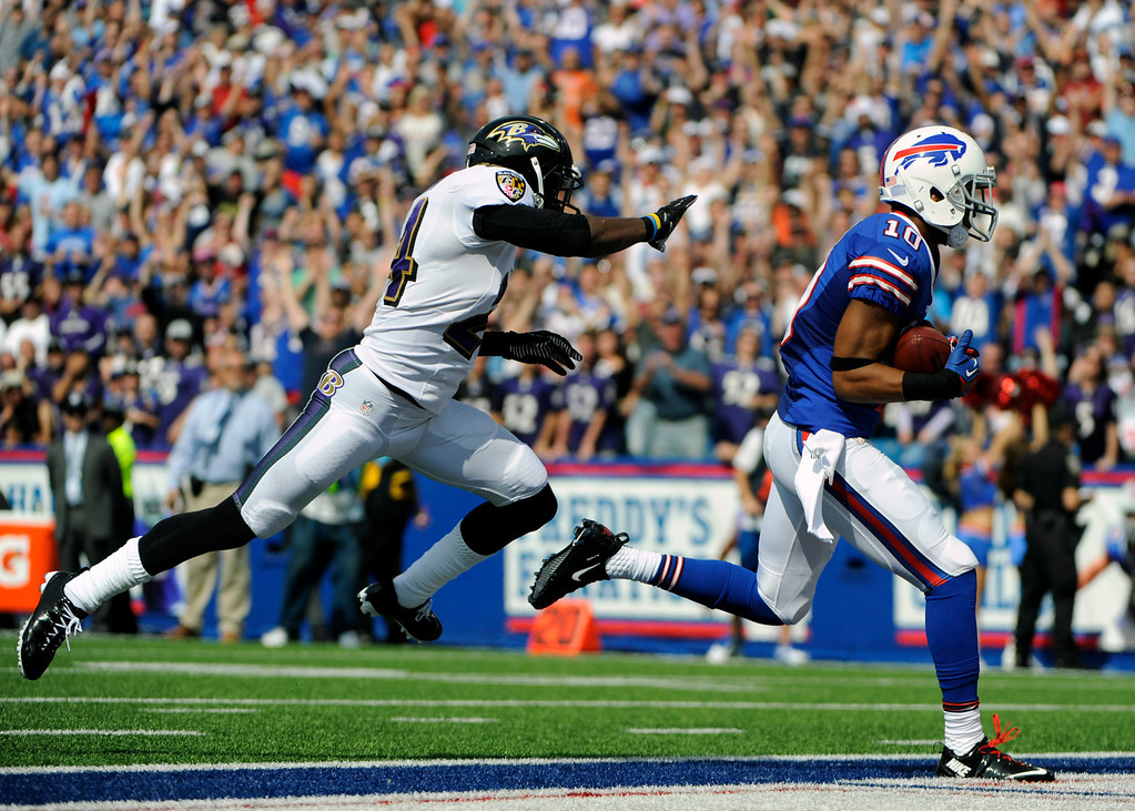 . Buffalo Bills wide receiver Robert Woods (10) scores a touchdown in front of Baltimore Ravens cornerback Corey Graham (24)  during the first half of an NFL football game on Sunday, Sept. 29, 2013, in Orchard Park, N.Y. (AP Photo/Gary Wiepert)