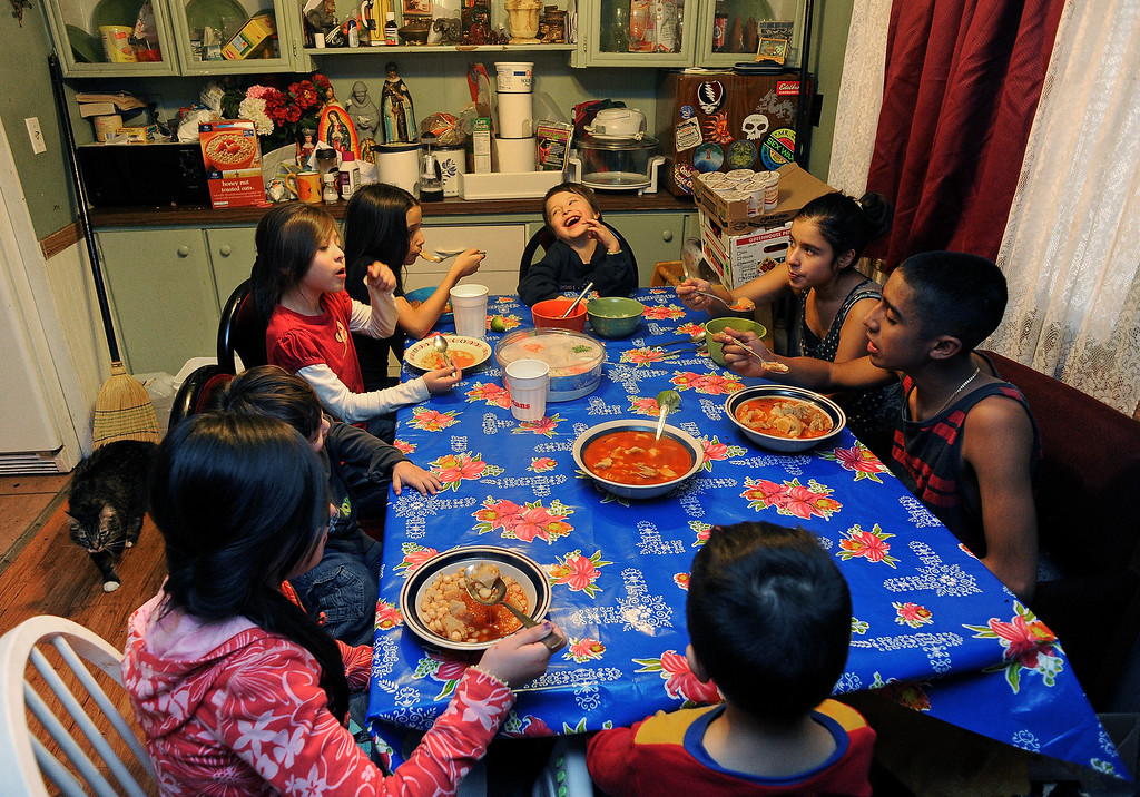 . GREELEY, CO - DECEMBER 16, 2013: The Moreno and Meza children have fun as they eat first and together before their parents at the Meza\'s tiny home in Greeley, CO on December 16, 2013. The children are from clockwise starting at the top of the table:  Jared Moreno, 5,  Genoveva Meza, 14, Martin Meza jr., 17, Sergio Meza, 3, Janeth Moreno, 10, in pink, Edwin Moreno, 2, Yanna Moreno, 8, Maria Meza, 11.  The Meza family, which consists of four children, Norma and her husband Martin have taken in the Moreno family after they lost everything in the September floods.  Rosario and her husband Jose have 5 children and are without a home at the moment.  Norma says she will help out her best friend for as long as she needs to.  The tiny house has 3 bedrooms and 2 small bathrooms and is home now to 14 people, 2 cats and 3 dogs.  (Photo By Helen H. Richardson/ The Denver Post)