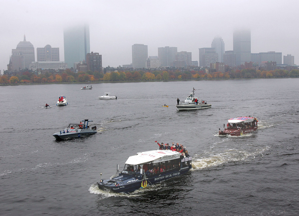 . Boston Red Sox players and officials wave to spectators from the Duck boats while motoring along the Charles River on the Cambridge, Mass. side during the Red Sox\'s World Series Championship parade, Saturday, Oct. 30, 2004. In the background is the Boston skyline.  (AP Photo/Chitose Suzuki))