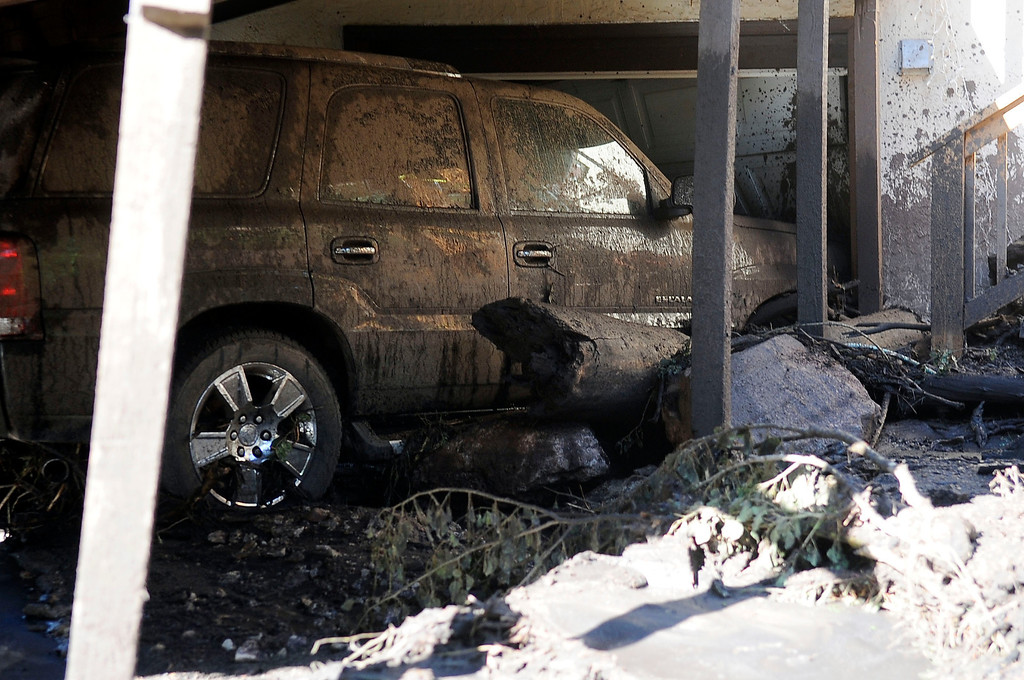 . Flooding that severely damaged numerous homes, businesses and this SUV along Canon Ave., was in the cleanup stage Tuesday morning.  (Photo By Steve Nehf / The Denver Post)