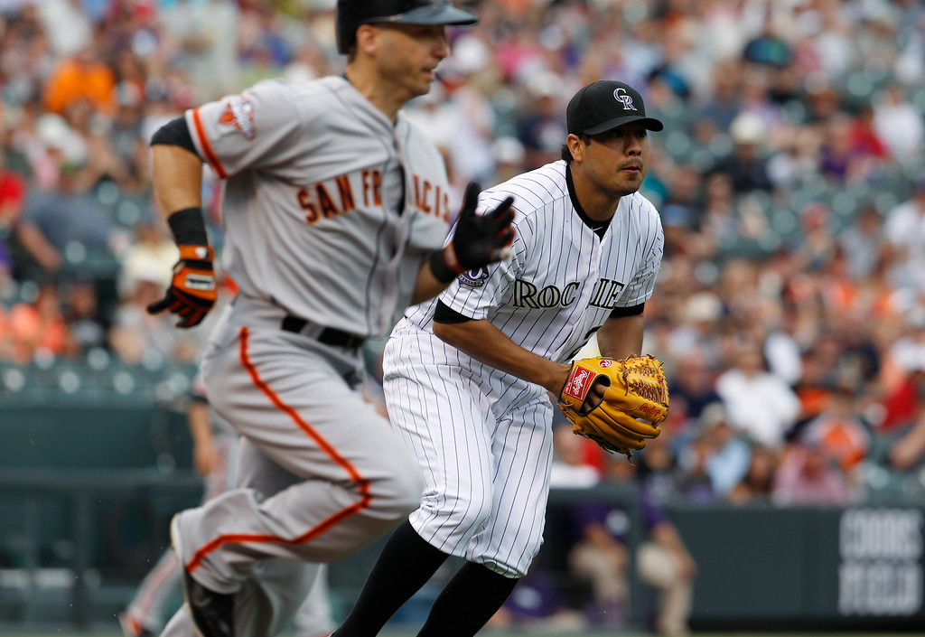 . Colorado Rockies starting pitcher Jorge De La Rosa, back, fields a sacrifice bunt off the bat of San Francisco Giants\' Tony Abreu in the first inning of a baseball game in Denver on Saturday, June 29, 2013. (AP Photo/David Zalubowski)