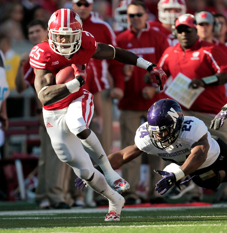 . Wisconsin running back Melvin Gordon runs for a first yard against Northwestern safety Ibraheim Campbell during the first half of an NCAA college football game in Madison, Wis., Saturday, Oct. 12, 2013. Wisconsin upset Northwestern 35-6. Gordon had 176 yards. (AP Photo/Andy Manis)