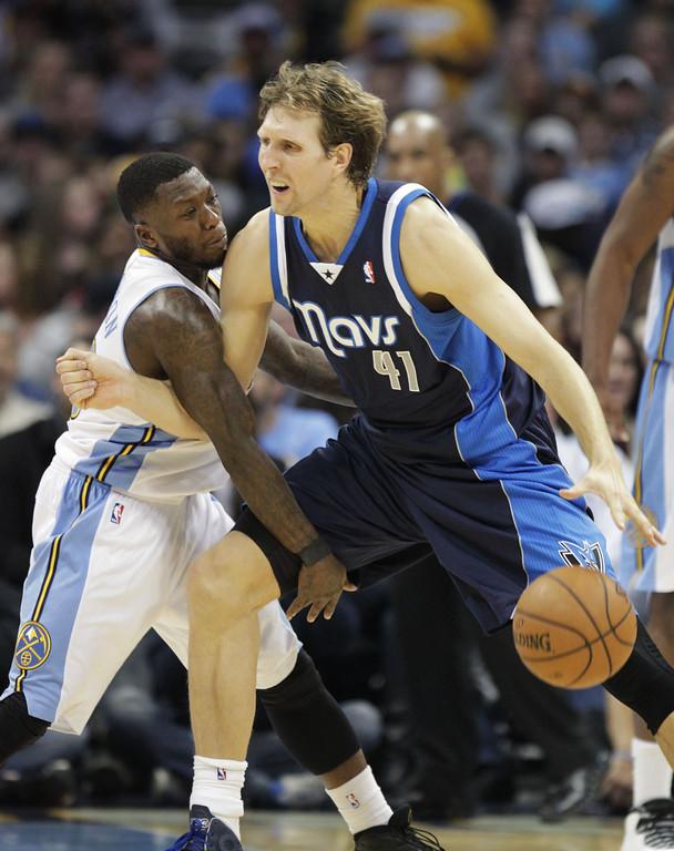 . Dallas Mavericks forward Dirk Nowitzki (41) drives against Denver Nuggets guard Ty Lawson (3) during the fourth quarter of an NBA basketball game in Denver on Saturday, Nov. 23, 2013. Denver won, 102-100. (AP Photo/Joe Mahoney)