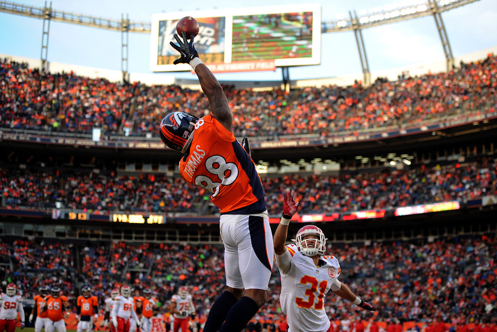 Description of . This is a favorite from the last game of the Broncos  season last year. At this very instant everyone in the stadium, fans, coaches, players, cheerleaders and especially the defender from Kansas City have their eyes on the ball and Demaryius Thomas's hand as he makes a leaping touchdown catch in their 11th straight win.  Denver Broncos wide receiver Demaryius Thomas (88) reaches up for the ball and catches it for a touchdown over Kansas City Chiefs free safety Tysyn Hartman (31) during the third quarter. The Denver Broncos vs Kansas City Chiefs at Sports Authority Field Sunday December 30, 2012. (Joe Amon, The Denver Post)