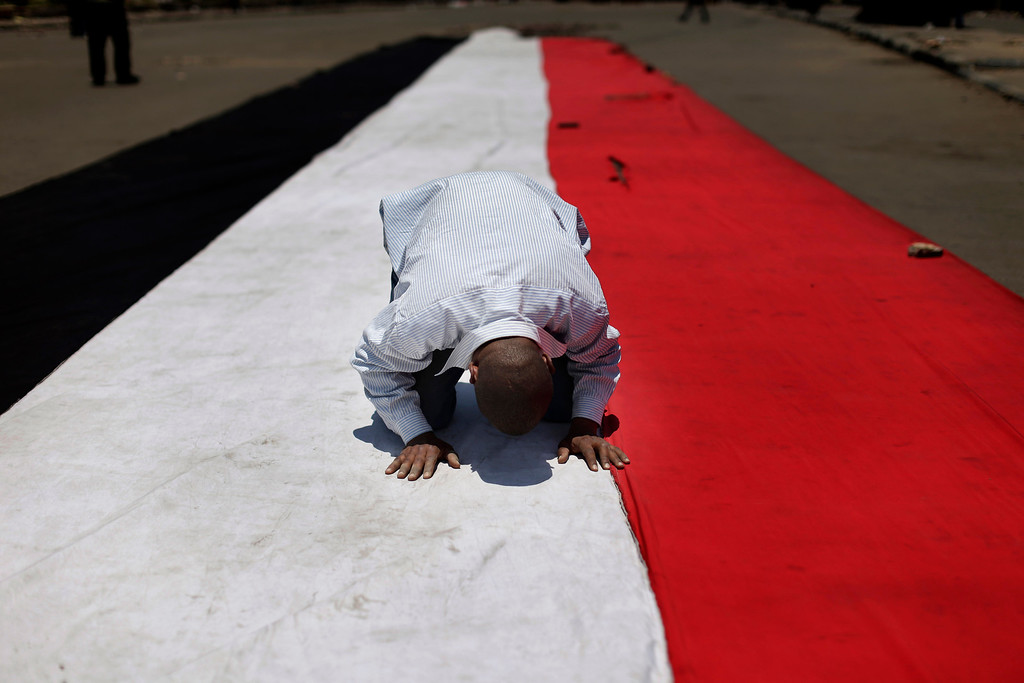 ". A supporter of ousted Egyptian President Mohammed Morsi prays on an Egyptian flag during the Friday prayer before a protest near the University of Cairo, Giza, Egypt, Friday, July 5, 2013. Tens of thousands, mainly Islamists, chanted ""down with military rule\"" in protests around the country Friday, venting their fury at the military for ousting President Mohammed Morsi and vowing to restore him to office. The first major attack by militants, in Sinai, hiked fears that the Islamists\' extreme fringe will turn to violent retaliation for Morsi\'s ouster.(AP Photo/Hassan Ammar)"