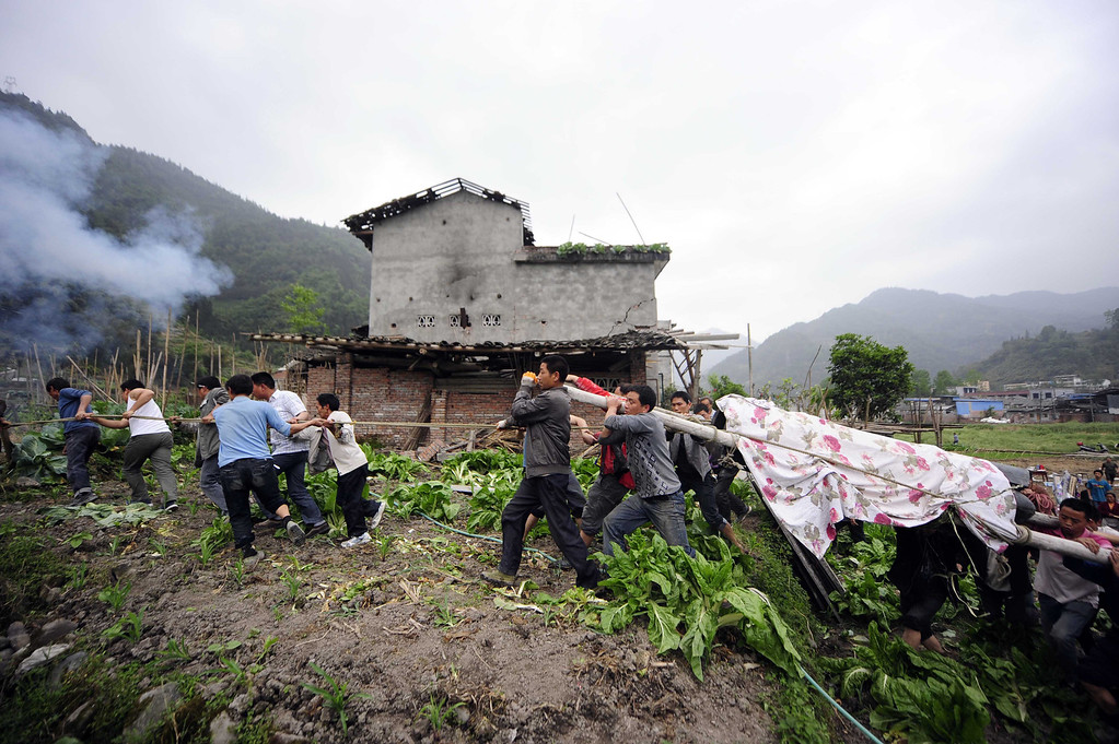 . This photo taken on April 21, 2013 shows residents carrying a coffin to the grave in disaster-hit Ya\'an, southwest China\'s Sichuan province.  STR/AFP/Getty Images