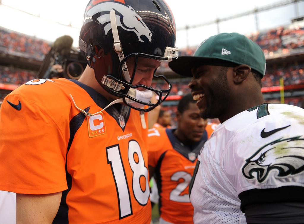 . Denver Broncos quarterback Peyton Manning (18) and Philadelphia Eagles quarterback Michael Vick (7) after the Broncos beat the Eagles 52-20. The Denver Broncos took on the Philadelphia Eagles at Sports Authority Field at Mile High in Denver on September 29, 2013. (Photo by Joe Amon/The Denver Post)