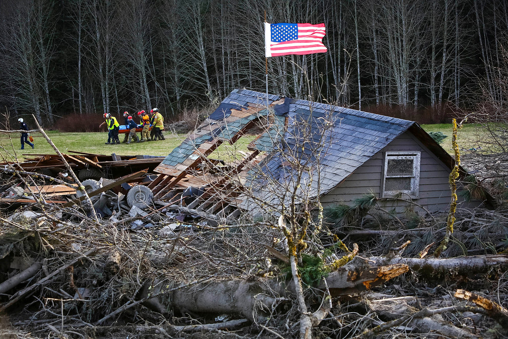 . Rescue workers remove a body from the wreckage of homes destroyed by a mudslide near Oso, Wash, Monday, March 24, 2014.  (AP Photo/seattlepi.com, Joshua Trujillo)