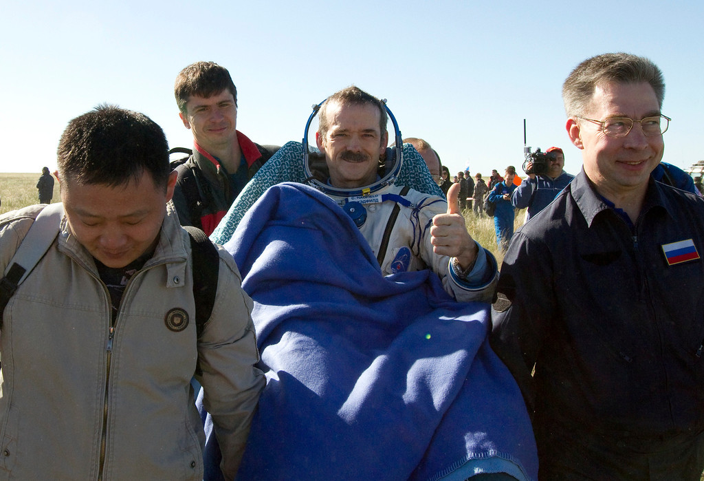 . Ground personnel carry Canadian astronaut Chris Hadfield, center, after the Russian Soyuz space capsule landed some 150 kilometers (94 miles) southeast of the town of Dzhezkazgan in central Kazakhstan, Tuesday, May 14, 2013.  (AP Photo/ Sergei Remezov, Pool)
