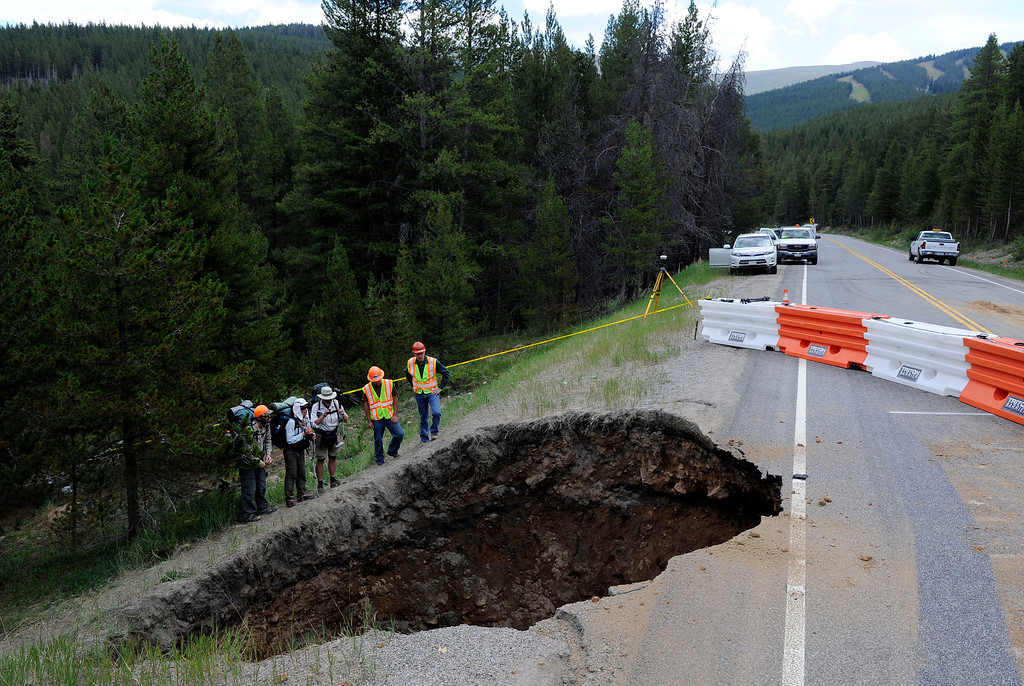 . Colorado Department of Transportation project engineers, Joe Elsen, fourth from left, and Matt Figgs, far right, offer hikers from left to right, Marlowe Kent, Lauren Jerd, and Shane O\'Donnell,  a safe, private look at large sinkhole Friday morning, July 13th, 2012 that opened up on highway 24 at mile marker 165, between Red Cliff and Leadville Colorado on Monday. The sinkhole, developed above a century-old Rio Grand Railway tunnel that measures 25x20 feet and approximately 50-60 feet deep. CDOT plans to put out the construction contract right away to begin repairs ASAP. The hikers are on a five-month trek across the Continental Divide. Andy Cross, The Denver Post