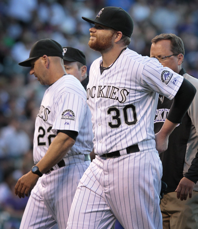 . Colorado Rockies starting pitcher Brett Anderson (30) holds his back as he leaves a game against the Chicago Cubs in the fourth inning of a baseball game in Denver on Tuesday, Aug. 5, 2014.Rockies manager Walt Weiss (22) talks to home plate umpire umpire Marty Foster.(AP Photo/Joe Mahoney)