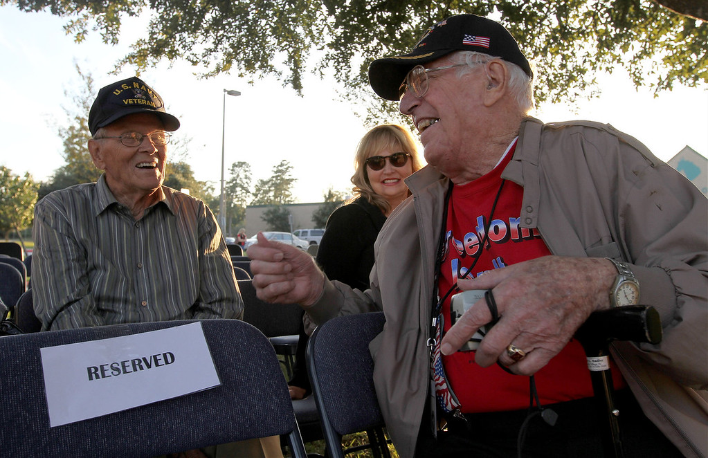 . World War II veterans Robert Sadler, right, and Irvin Marshall laugh as they swap service stories during a Veterans Day celebration at the Veterans Honor Garden at Creekwood Middle School Monday, Nov. 11, 2013, in Kingwood, Texas. (AP Photo/ The Courier, Jason Fochtman)