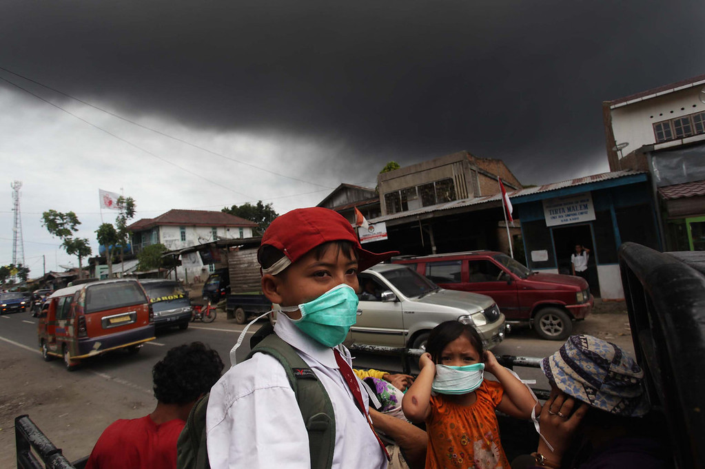 . Residents of Karo district leave as an ash cloud rises during a fresh eruption of the Mount Sinabung volcano on September 17, 2013. Thousands of villagers fled after Mount Sinabung\'s series of volcanic eruptions on Indonesia\'s Sumatra island, spewing rocks and red-hot ash onto surrounding villages, officials said.   ADE SINUHAJI/AFP/Getty Images