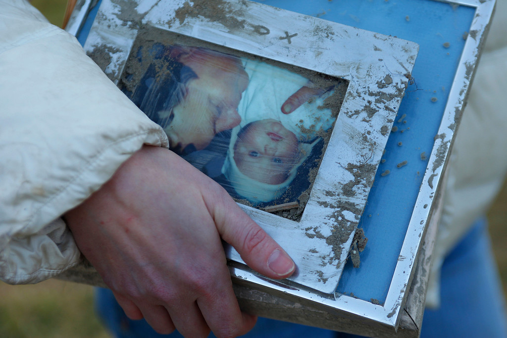 . A woman holds family photos pulled from the rubble at the site of Saturday\'s fatal mudslide near Oso, Wash., Sunday, March 23, 2014. (AP Photo /The Herald, Genna Martin)