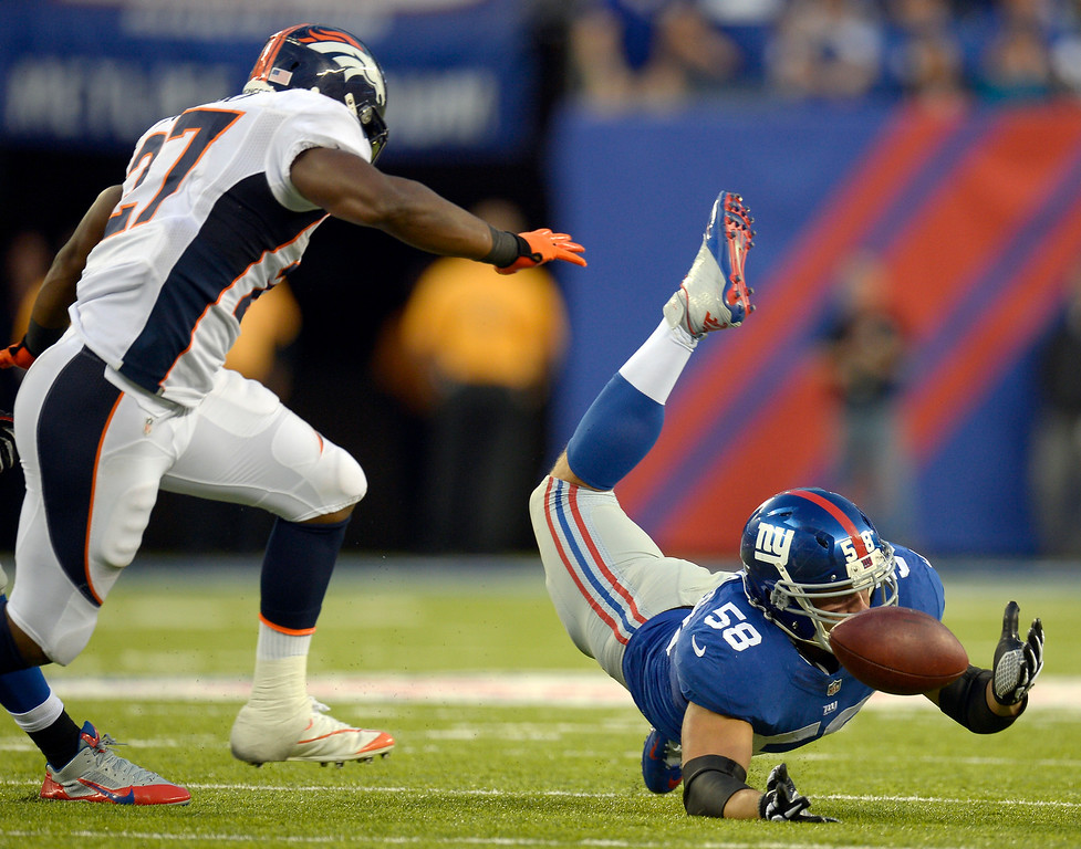 . New York Giants middle linebacker Mark Herzlich (58) dives after a loose ball as the ball bounces around and in to the hand of Denver Broncos running back Knowshon Moreno (27) during the third quarter September 15, 2013 MetLife Stadium. Knowshon Moreno picked up the ball and ran for 5 yards on the play. (Photo by John Leyba/The Denver Post)