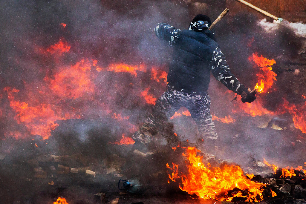. A protester prepares to throw a Molotov cocktail during clashes with police in central Kiev, Ukraine, Wednesday, Jan. 22, 2014. (AP Photo/Evgeny Feldman)