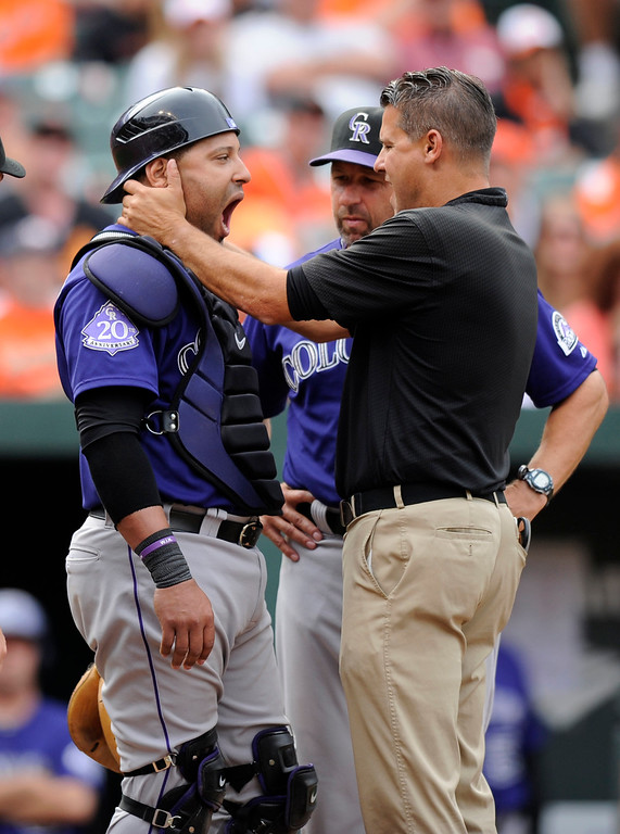 . Colorado Rockies catcher Yorvit Torrealba, left, is checked out by a trainer after he was hit by a ball as manager Walt Weiss, center, looks on during the eighth inning of a baseball game against the Baltimore Orioles, Sunday, Aug. 18, 2013, in Baltimore. The Orioles won 7-2. (AP Photo/Nick Wass)