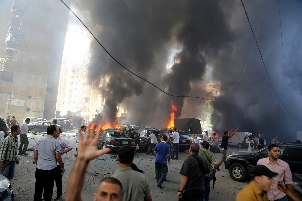 . Smoke rises from burnt cars as members of Hezbollah shout after an explosion in Beirut\'s southern suburbs July 9, 2013.  REUTERS/ Issam Kobeisi