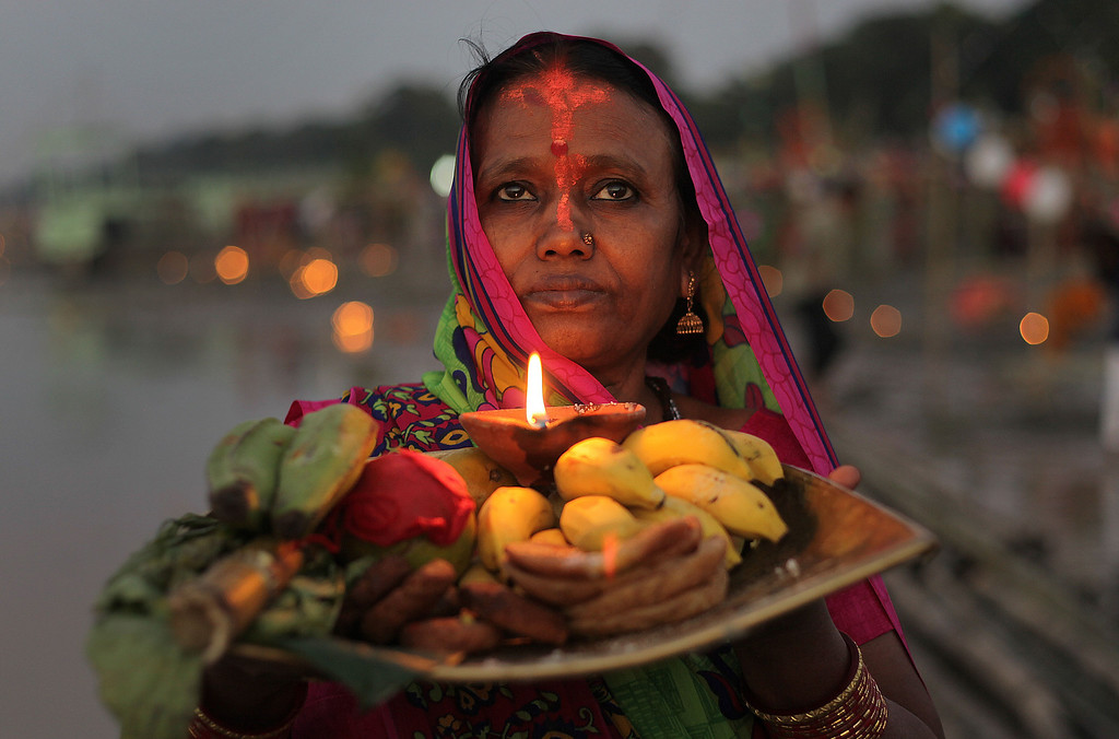 . A Hindu devotee performs rituals to the setting sun in the River Brahmaputra during Chhath Puja festival in Gauhati, India, Friday, Nov. 8, 2013. . Chhath prayers, an ancient Hindu festival popular amongst the working class, is performed to thank the Sun God for sustaining life on earth. (AP Photo/Anupam Nath)