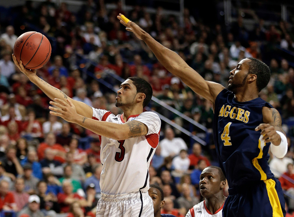 . Louisville guard Peyton Siva (3) drives to the basket as North Carolina A&T forward DaMetrius Upchurch (4) defends during the second half of a second-round game in the NCAA college basketball tournament, Thursday, March 21, 2013, in Lexington, Ky. (AP Photo/John Bazemore)