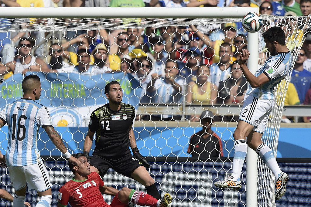 . Iran\'s goalkeeper Alireza Haqiqi (C) defends as Argentina\'s defender Ezequiel Garay (R) makes an attempt on goal during the Group F football match between Argentina and Iran at the Mineirao Stadium in Belo Horizonte during the 2014 FIFA World Cup in Brazil on June 21, 2014. JUAN MABROMATA/AFP/Getty Images