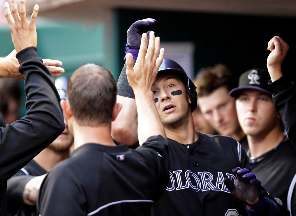 . Colorado Rockies\' Troy Tulowitzki is congratulated in the dugout after hitting a solo home run off Cincinnati Reds starting pitcher Johnny Cueto in the fourth inning of a baseball game on Friday, May 9, 2014, in Cincinnati. (AP Photo/Al Behrman)