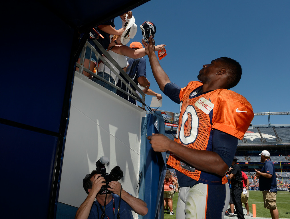 . Denver Broncos WR, Emmanuel Sanders, signs autographs for fans after autographing it for a fan after practice and scrimmage at Sports Authority Field at Mile High Saturday afternoon, August 02, 2014. (Photo By Andy Cross / The Denver Post)