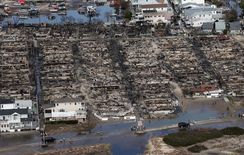 . People gather around the remains of burned homes after Superstorm Sandy on October 31, 2012 in the Breezy Point neighborhood of the Queens borough of New York City. Over 50 homes were reportedly destroyed in a fire during the storm. At least 50 people were reportedly killed in the U.S. by Sandy. New York City was hit especially hard with widespread power outages and significant flooding in parts of the city. (Photo by Mario Tama/Getty Images)