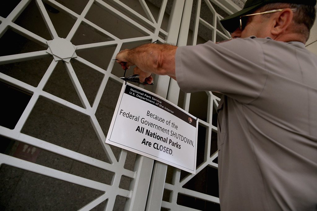 . U.S. Park Service employee puts a closed sign on the restrooms at the World War II Memorial ticket office on the National Mall October 1, 2013 in Washington, DC. National Park Service park facilities and grounds were closed and more than 21,000 of the service\'s employees were furloughed after Congress was unable to agree on a federal budget and shut down for the first time in 17 years.  (Photo by Chip Somodevilla/Getty Images)