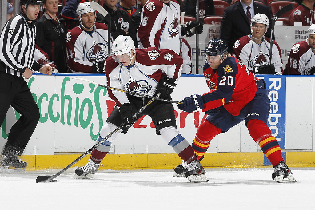 . SUNRISE, FL - JANUARY 24: Tyson Barrie #4 of the Colorado Avalanche and Sean Bergenheim #20 of the Florida Panthers battle for control of the puck during first period action at the BB&T Center on January 24, 2014 in Sunrise, Florida. (Photo by Joel Auerbach/Getty Images)