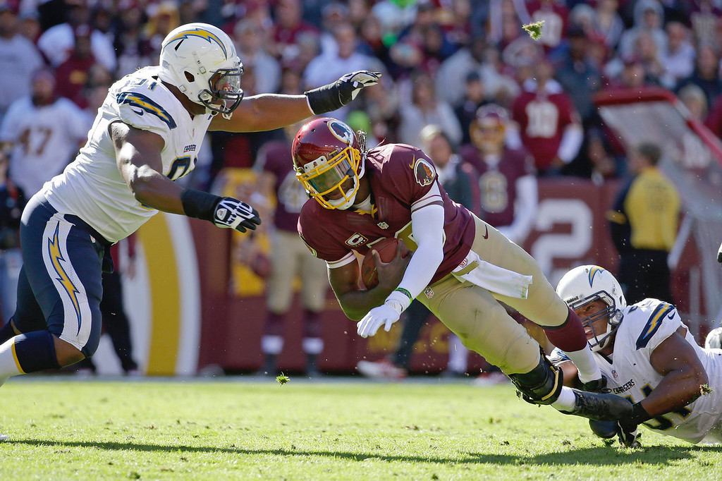 . Washington Redskins quarterback Robert Griffin III is stopped by San Diego Chargers defensive end Kendall Reyes, left, and outside linebacker Larry English, right, during the first half of a NFL football game in Landover, Md., Sunday, Nov. 3, 2013. (AP Photo/Alex Brandon)
