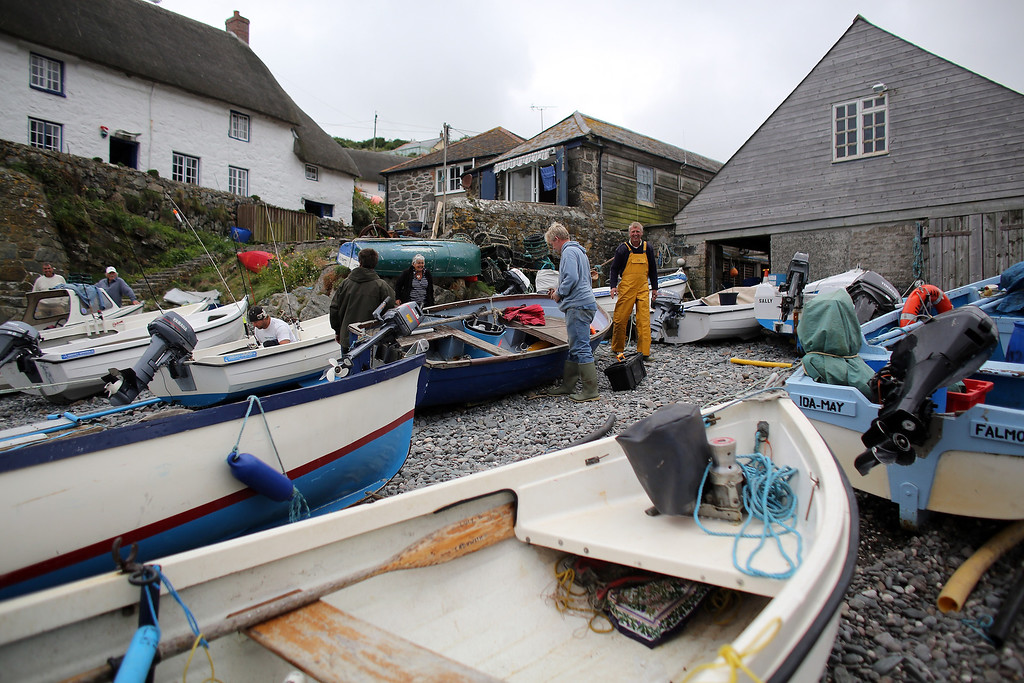 . CADGWITH, ENGLAND - SEPTEMBER 05:  Fishermen prepare their boats and kit prior to the final fortnightly fishing competition of the year in Cadgwith on September 5, 2013 in Cornwall, England. The summertime competition to catch the heaviest fish of a chosen type, (for this final the fish was bass) allows locals and visitors the chance to fish for fun and a cash prize, with the catch cooked in a pot at the end of the night on some occasions. Set on the Lizard peninsula in Cornwall, the village of Cadgwith, which was established in medieval times, owes its existence to the fishing industry. However, whilst fishing remains an important part of village life today, tourism is also now a major source of income for the inhabitants. (Photo by Matt Cardy/Getty Images)