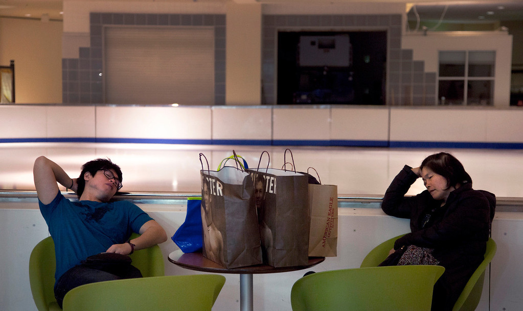. Nick Cheung, 20, left, and his mother, Yau Cheung, doze while waiting for other relatives to finish shopping at the Lloyd Center Mall in Northeast Portland early Friday, Nov. 29, 2013. Black Friday, the day after Thanksgiving, is typically the nation\'s biggest shopping day of the year. (AP Photo/The Oregonian, Beth Nakamura)