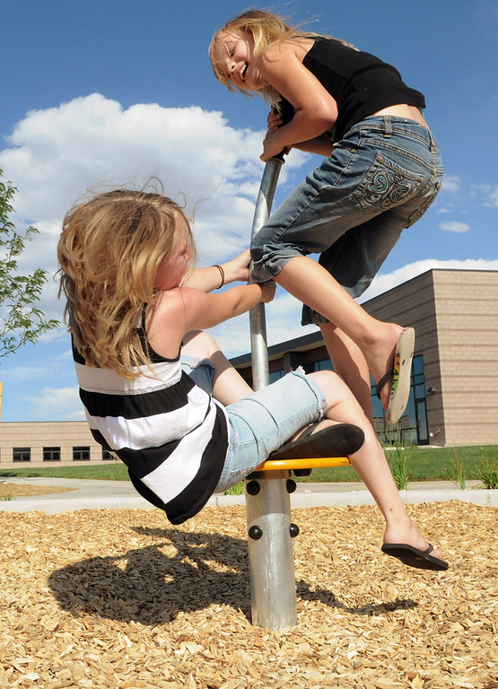 . Kaitlyn Schnell, 7, left, and Melanie Solovyeva, 8, both of Brighton, laugh as they spin on a platform in a play area behind Anythink Wright Farms library branch last week in Thornton. The Wright Farms Metro District funded the park, which features educational gardens, walking paths and a play area. (KRISTIN MORIN / YOURHUB)