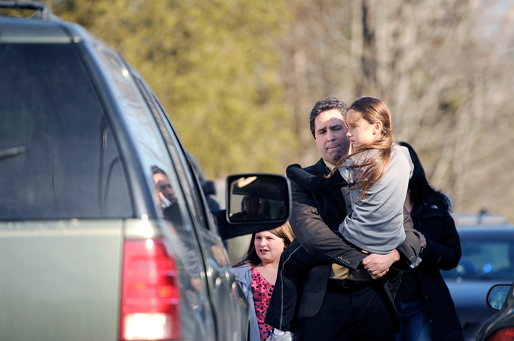 . People leave the scene of a shooting incident at Sandy Hook Elementary School in Newtown, Connecticut, in this December 14, 2012 handout photo. Twenty-six people, including 20 children, have been killed in a shooting at Sandy Hook Elementary School in Newtown, Connecticut.  REUTERS/John Woike/Hartford Courant/Handout