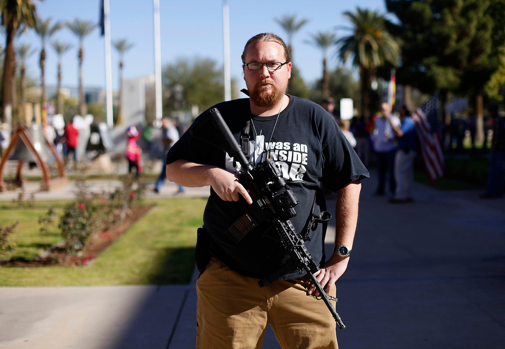 """. Brandon Smith poses with his AR-15 rifle during a pro-gun and Second Amendment protest outside the Arizona State Capitol in Phoenix, Arizona January 19, 2013. Pro-gun activists held \""""high noon\"""" rallies across the United States to defend the right to own firearms that they say is being threatened by U.S. President Barack Obama\'s gun-control proposals. REUTERS/Joshua Lott"""
