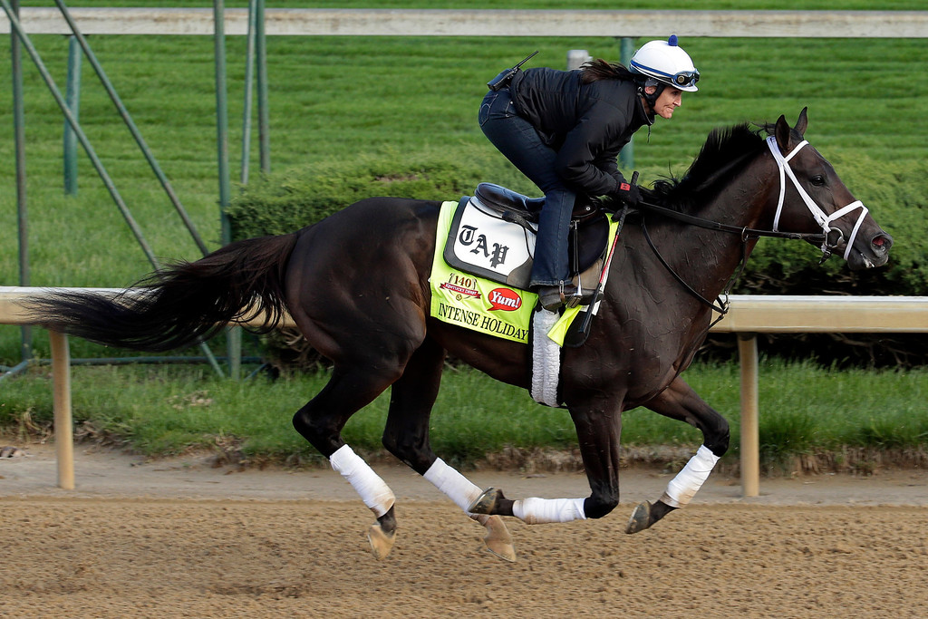 . Exercise rider Isabelle Bourez takes Kentucky Derby entrant Intense Holiday for a morning workout at Churchill Downs Thursday, May 1, 2014, in Louisville, Ky. (AP Photo/Charlie Riedel)