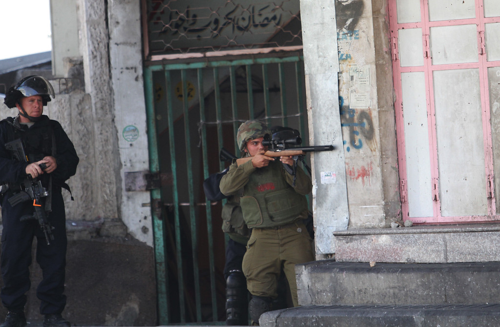 . An Israeli soldier aims his weapon during clashes with Palestinians following a protest against the Israeli military action in Gaza, in the West Bank city of Hebron, Friday, Aug. 1, 2014. (AP Photo/Nasser Shiyoukhi)