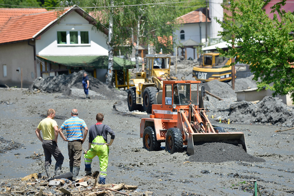 . Heavy machinery is used to clean streets in the village of Topcic Polje, that was damaged in a landslide, near the Bosnian town of Zenica, 90 kilometers north of Sarajevo, on Monday May 19, 2014. At least 35 people have died in Serbia and Bosnia in the five days of flooding caused by unprecedented torrential rain, laying waste to entire towns and villages and sending tens of thousands of people out of their homes, authorities said. (AP Photo/Sulejman Omerbasic)