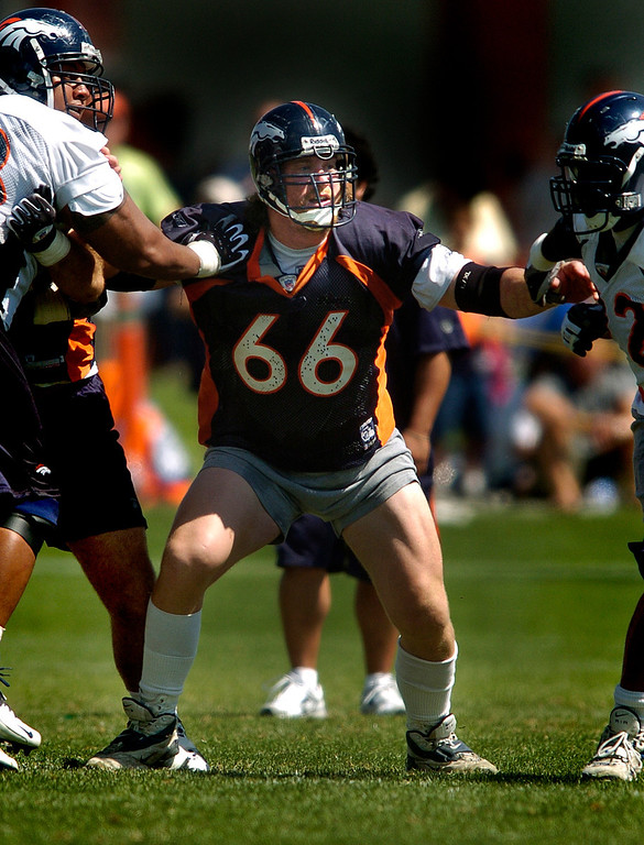 . Tom Nalen, center, holds back the defence,Wednesday, August, 3, 2005, during the morning section of Broncos camp at Dove Valley. RJ Sangosti/ The Denver Post