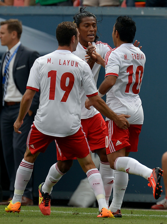 . Marco Fabian #10 of Mexico celebrates his goal with Joel Huiqui #4 of Mexico and Miguel Layun #19 in the first half of the CONCACAF Gold Cup soccer game July 14, 2013 at Sports Authority Field at Mile High. (Photo By John Leyba/The Denver Post)