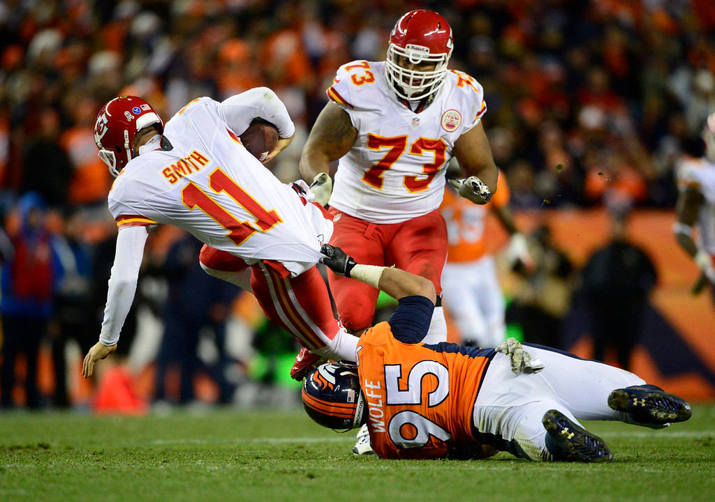 . Kansas City Chiefs quarterback Alex Smith (11) is tackled by Denver Broncos defensive end Derek Wolfe (95) in the third quarter.  The Denver Broncos take on the Kansas City Chiefs at Sports Authority Field at Mile High in Denver on November 17, 2013. (Photo by AAron Ontiveroz/The Denver Post)
