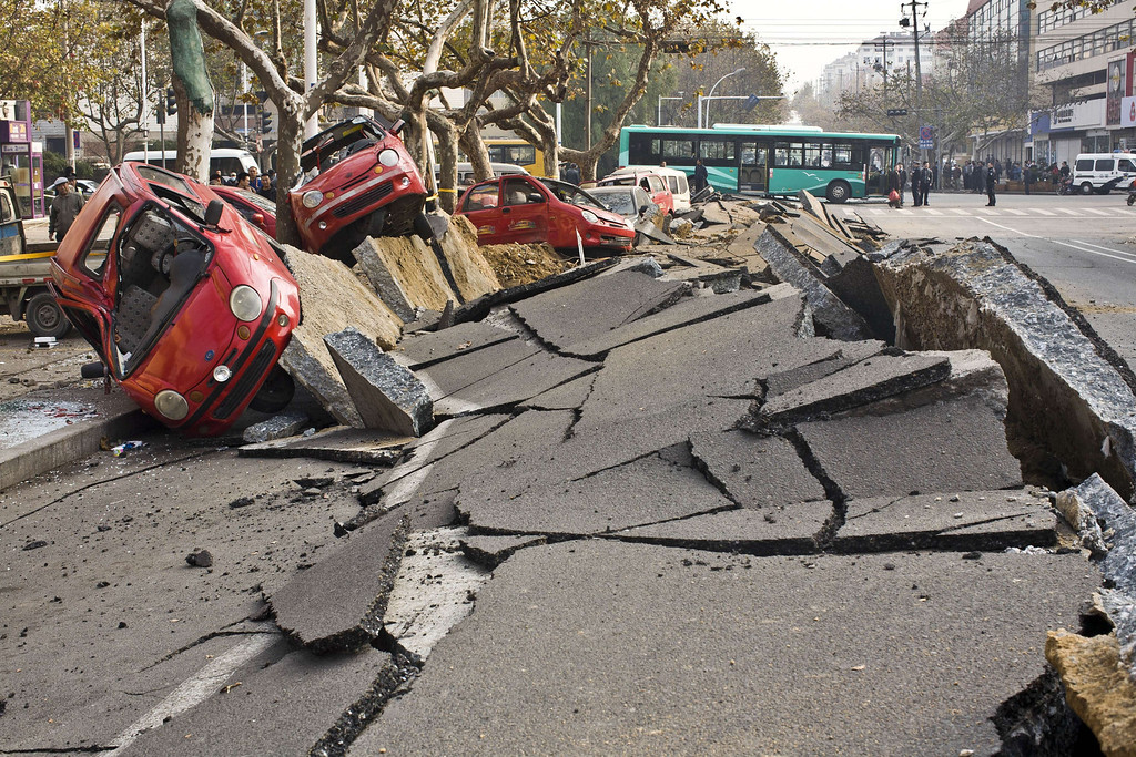 . Damaged vehicles lie by a street after an oil pipeline exploded, ripping roads apart, turning cars over and sending thick black smoke billowing over the city of Qingdao, east China\'s Shandong province on November 22, 2013, killing 35 people, authorities said, in the latest deadly industrial accident in the country. T    AFP PHOTOSTR/AFP/Getty Images